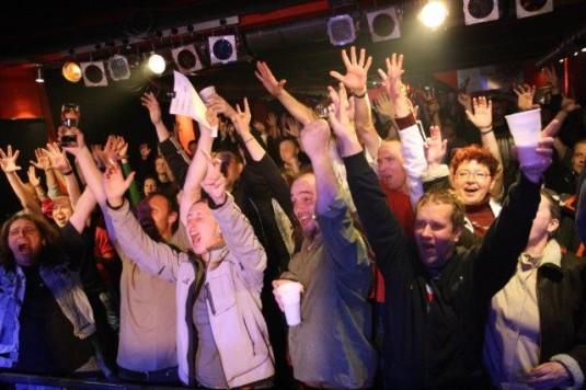 Publikum během benefičního koncertu natáčí zdravici pro zraněného muzikanta.